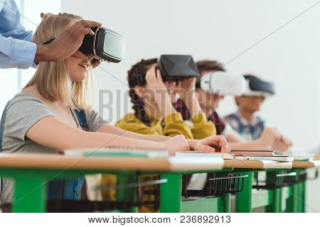 Cropped Image Of African American Teacher Adjusting Virtual Reality Headset To Teenage Schoolgirl Wi