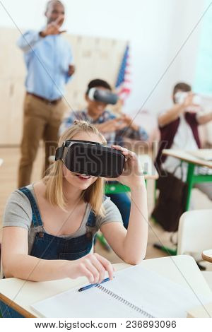 Teenage Schoolgirl Using Virtual Reality Headset With Male Classmates And Teacher Behind