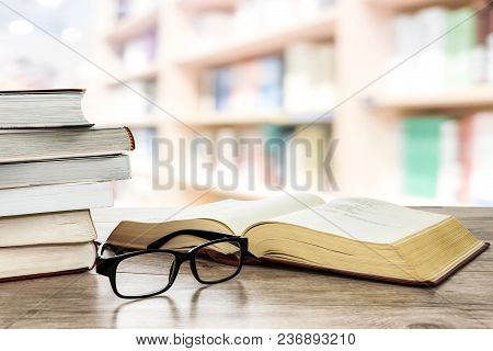 Concept Image Of Education And Learning - Stocks Of Books Next To Open Book And Eyeglasses On A Desk