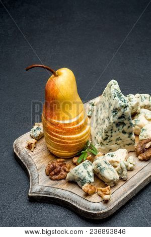Slice Of French Roquefort Cheese And Figs On Wooden Cutting Board