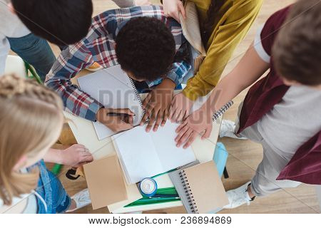 Top View Of High School Students Helping Their Classmate With Homework