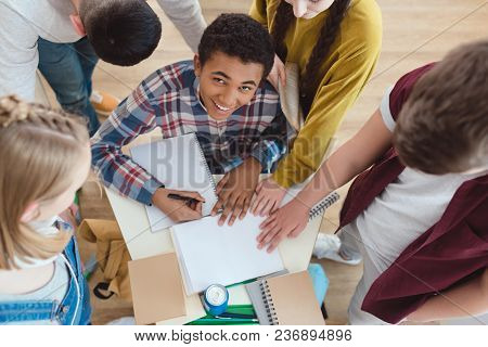 High Angle View Of High School Students Helping Their Classmate With Homework