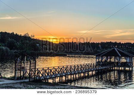 Wooden Footbridge With A Gazebo On The Evening Lake Shore. Sunset.