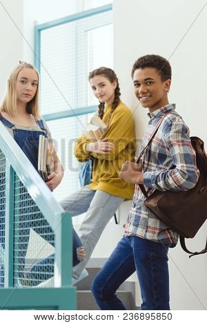 Happy High School Students Standing On Stairs At School And Looking At Camera