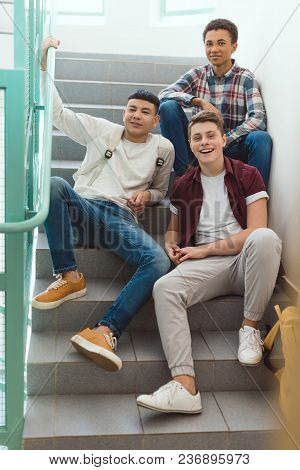 Teenage Schoolboys Sitting On Stairs At School And Looking At Camera