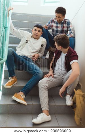 Teenage Schoolboys Sitting On Stairs At School