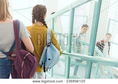 Rear View Of Teen Students With Backpacks Walking Down Stairs At School Corridor