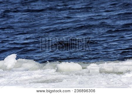 Blocks Of Ice In The Water. Ice Pressed Against The Coast By Waves And Wind.