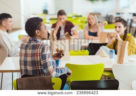 Group Of High School Students Chatting While Taking Lunch At School Cafeteria
