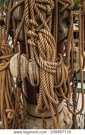 Rolled Rope And Pulleys Supported On The Central Mast Of A Sailing Ship On A Cloudy Day In Amsterdam