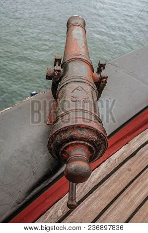 Close-up Of Old Iron Cannon On Wooden Bulwark In Sailboat Docked At Canal Of Amsterdam. Famous For I