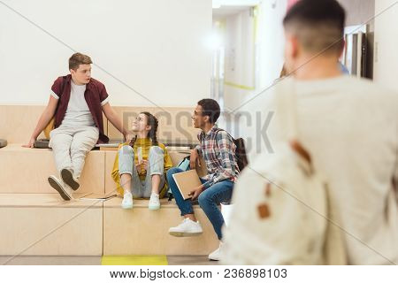 Group Of High School Students Sitting At School Corridor And Chatting