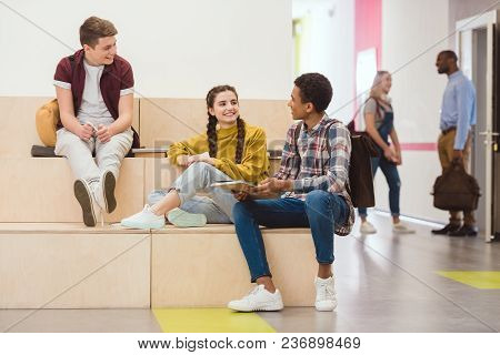 High School Students Sitting In Lounge Zone At School Corridor