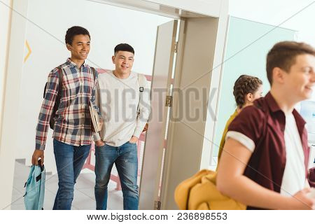 Multiethnic High School Students Walking By School Corridor