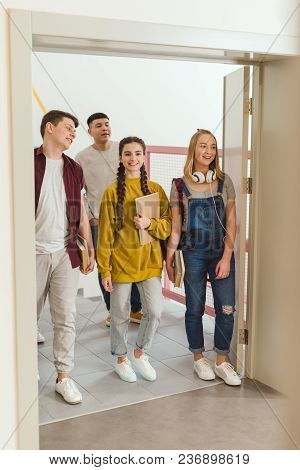 Happy Teenage High School Students Walking By School Corridor