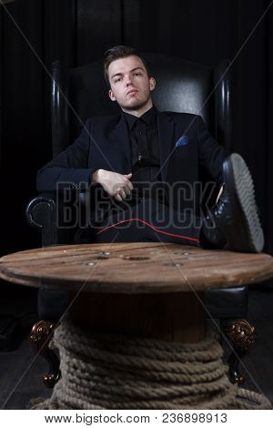A Young Man In A Suit On The Background Of An Expensive Dark Interior With A Place For Advertising O