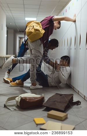 Frightened Asian Schoolboy Being Bullied In School Corridor