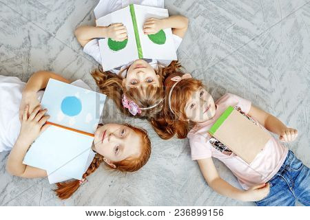 Three Children Of Students Read Book. Flat Lay. The Concept Of Lifestyle, Childhood, Education, Fami