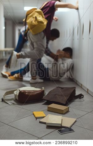 Blurred Shot Of Schoolboy Being Bullied By Classmates In School Corridor Under Lockers With Spilled