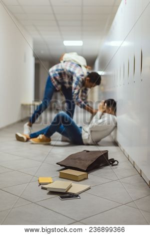 Schoolboy Being Bullied By Classmate In School Corridor Under Lockers With Spilled Books From Backpa