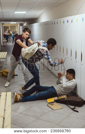 Asian And African American Schoolboys Being Bullied In School Corridor By Their Classmate