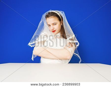 Studio Portrait Of A Beautiful Amusing Bride Against A Bright Background
