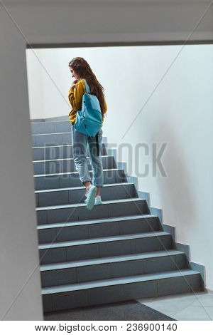 Rear View Of Schoolgirl With Backpack Walking Upstairs