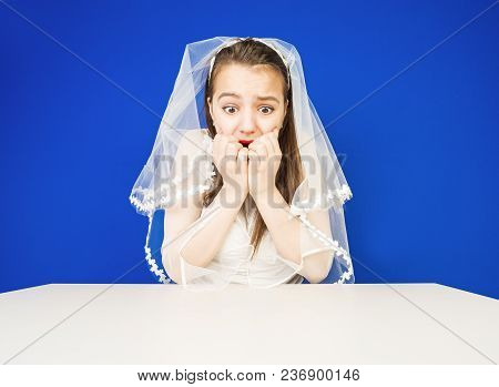 Surprised And Amazed Bride Looking Down At The Table. Expressive Facial Expressions.