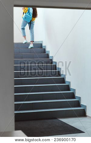 Rear View Of Schoolgirl Walking Upstairs In School Corridor