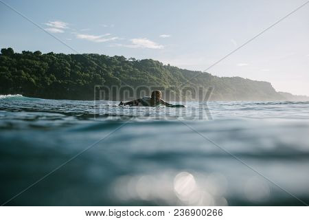 Young Man Swimming On Surfboard On Sunny Day