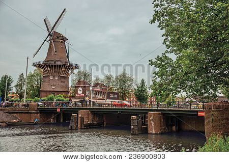 Amsterdam, Northern Netherlands - June 25, 2017. Bridge Over Canal, Trees And Old Windmill On The Ba