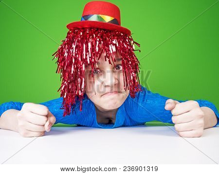 Comedy Humorous Joke For People. Portrait Of A Cute Restless Girl In A Wig Which Grimaces On A Green