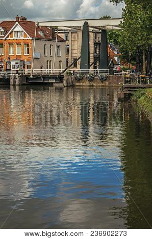 Clouds And Sky Reflected In Canal Water Surface, Buildings And Bascule Bridge On A Sunny Day In Wees