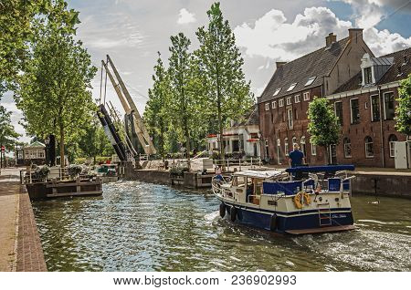 Weesp, Northern Netherlands - June 26, 2017. Boat Passing By A Tree-lined Wide Canal On Cloudy Day I