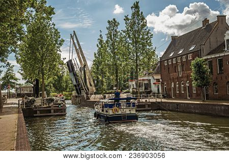 Boat Passing By A Tree-lined Narrow Canal With A Raised Bascule Bridge In The Sunrise At Weesp. Quie