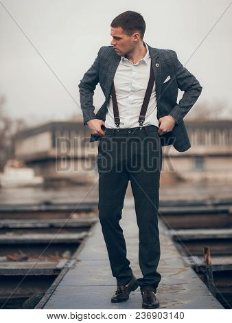 Уoung Man In Suit, White Shirt And Suspenders On His Trousers Walks On Pier.