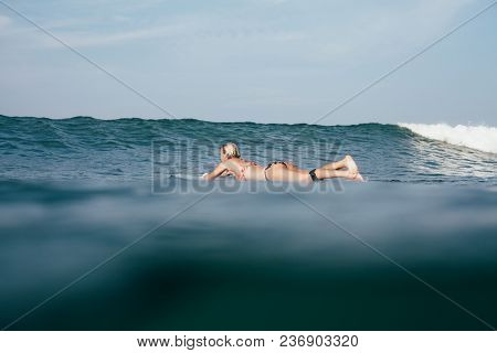 Young Woman In Bikini Swimming On Surfboard
