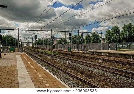 Platform, Railroad Rails And Signaling At Train Station Under Blue Cloudy Sky At Weesp. Quiet And Pl