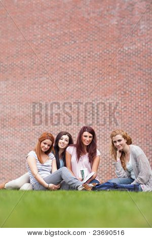Portrait of friends posing with a book while sitting on the lawn