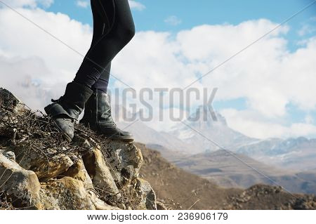 Close-up Of Female Feet In Vintage Boots Stand On A Rock In The Mountains Against The Background Of
