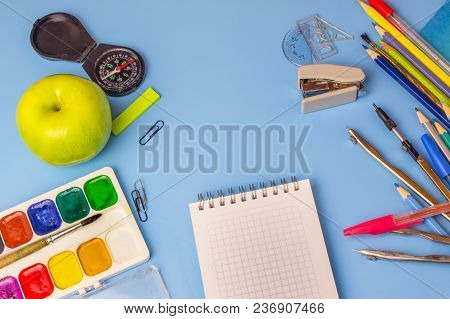 A Schoolboy's Table. School Supplies On A Blue Background. Template Ready For Your Design