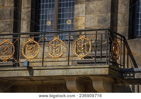 Close-up Of Facade With Balcony And Golden Iron Balustrade In The Royal Palace Of Amsterdam. The Cit