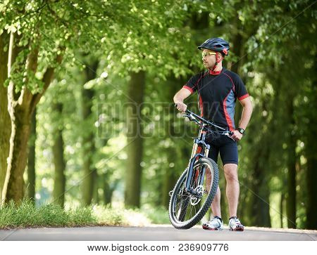 Handsome Male Biker In Professional Sportswear Clothing And Protective Helmet Looking Far In Distanc