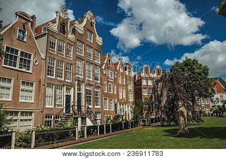 Semidetached Typical Houses And Green Garden At Begijnhof, A Medieval Semi-monastic Community In Ams