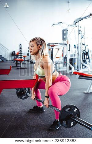 Girl In The Gym Engaged In Fitness Raises The Bar
