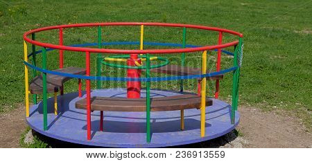 Children's Iron Carousel. Children's Playground. Swing, Carousel And Slide