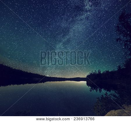 Lake At Night With Amazing Starry Sky And Reflections In The Water. Natural Outddors Travel Dark Bac