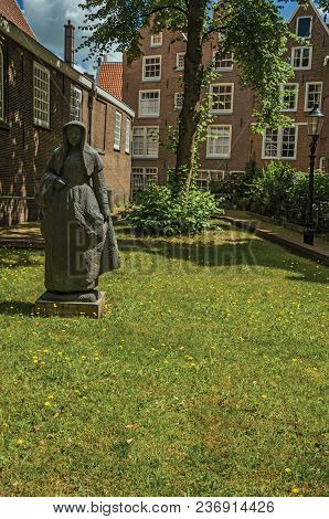 Typical Brick Houses, Statue And Green Garden At Begijnhof, A Medieval Semi-monastic Community In Am