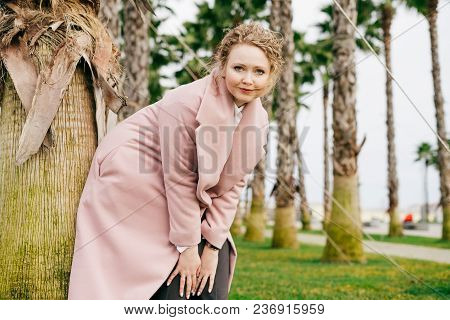 Beautiful Young Woman In A Pink Coat Walking Along The Park Next To Tall Green Palms