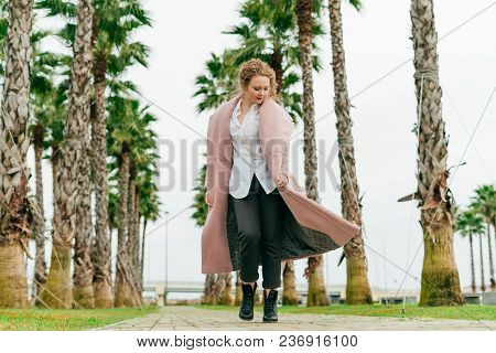 A Young Stylish Woman In A Coat Walks Along The Green Park, Enjoying Spring And Warmth
